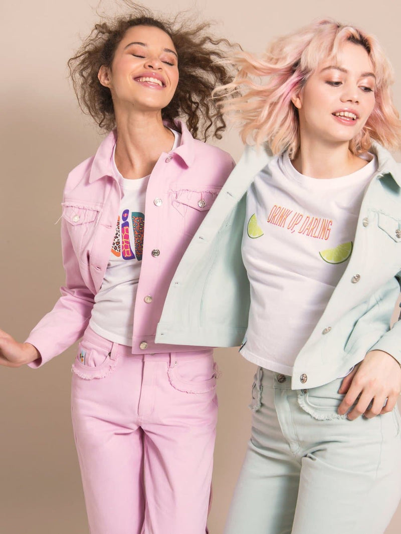Two happy women wearing denim jackets in light pink and light blue and white tees with prints