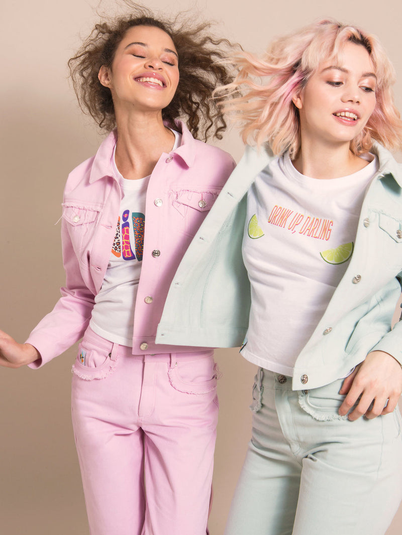 Two women wearing denim sets - one in light blue and one in light pink, with white tees underneath