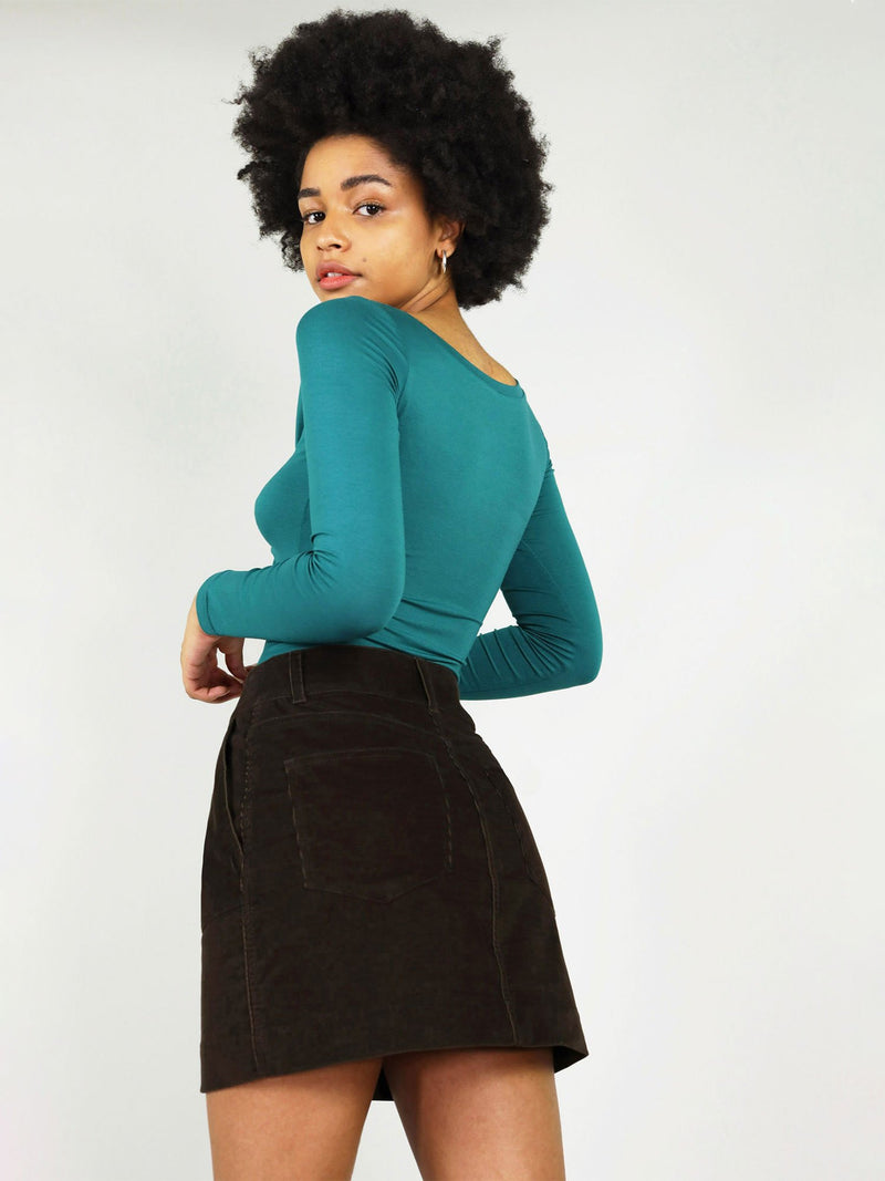 Close up side and back view of size xs, classic black corduroy skirt. It has mini length, belt loops and two large back pockets.