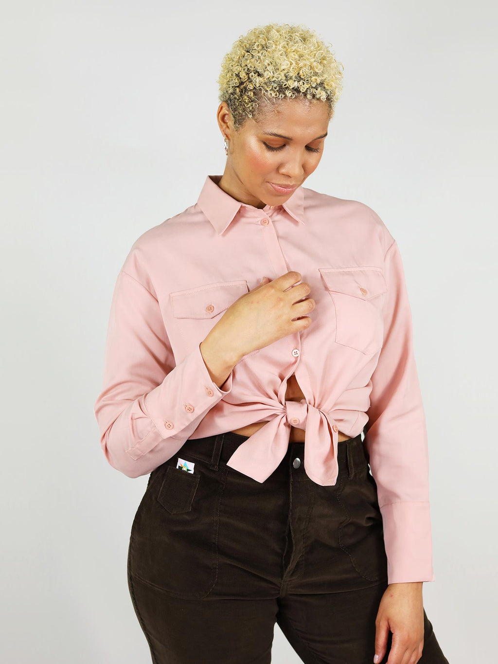 Close-up shot of the blushing pink, summer shirt. It has comfortable fit, two front large pockets, buttoned down and can be tied up in the middle for a sexier look.