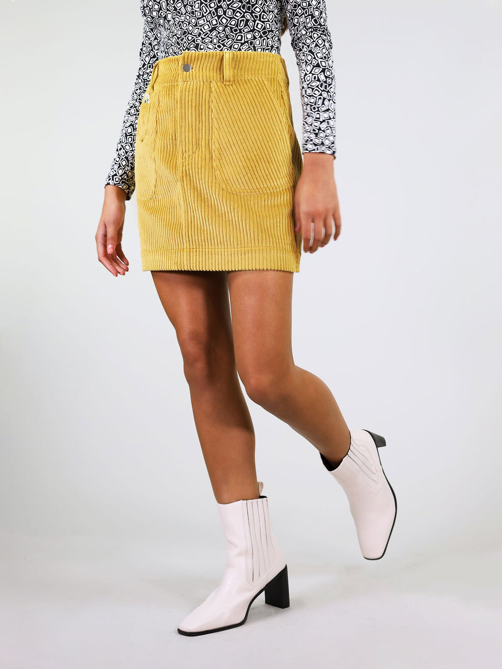 Corduroy skirt in mustard yellow, mini length. Large front and back pockets with belt loops and button fastening. Stretchy 100% cotton, perfect to tuck in a shirt and woven logo on the left pocket.