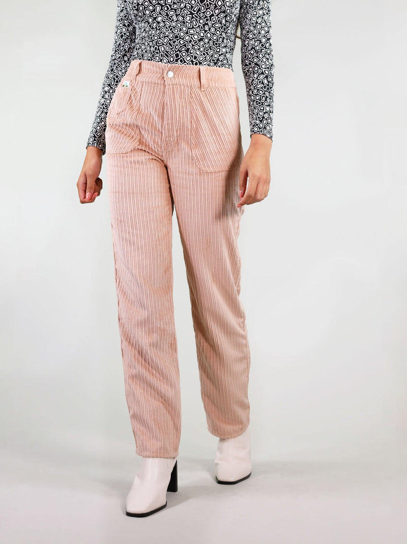 Close up view of the corduroy trousers in pastel pink. These have straight leg fit and hight waist with large side pockets. Signature logo on the left front and belt loops.