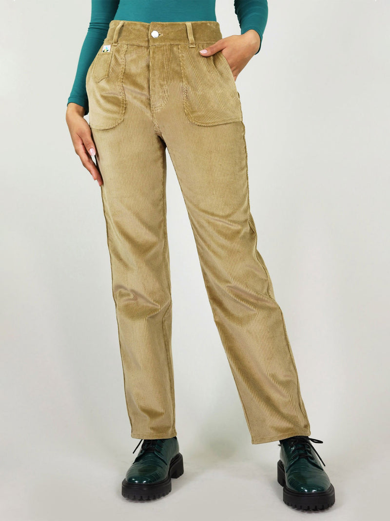 Closer view at the high waist corduroy trousers in autumn beige. Loose fit, easy to tuck in a shirt. Large side pockets with signature logo on the left side and belt loops.