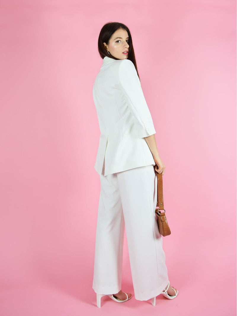 Backshot of blonde gone rogue's girlboss white sustainable trouser suit. The pant suit consists from a white longline blazer and wide leg trousers.