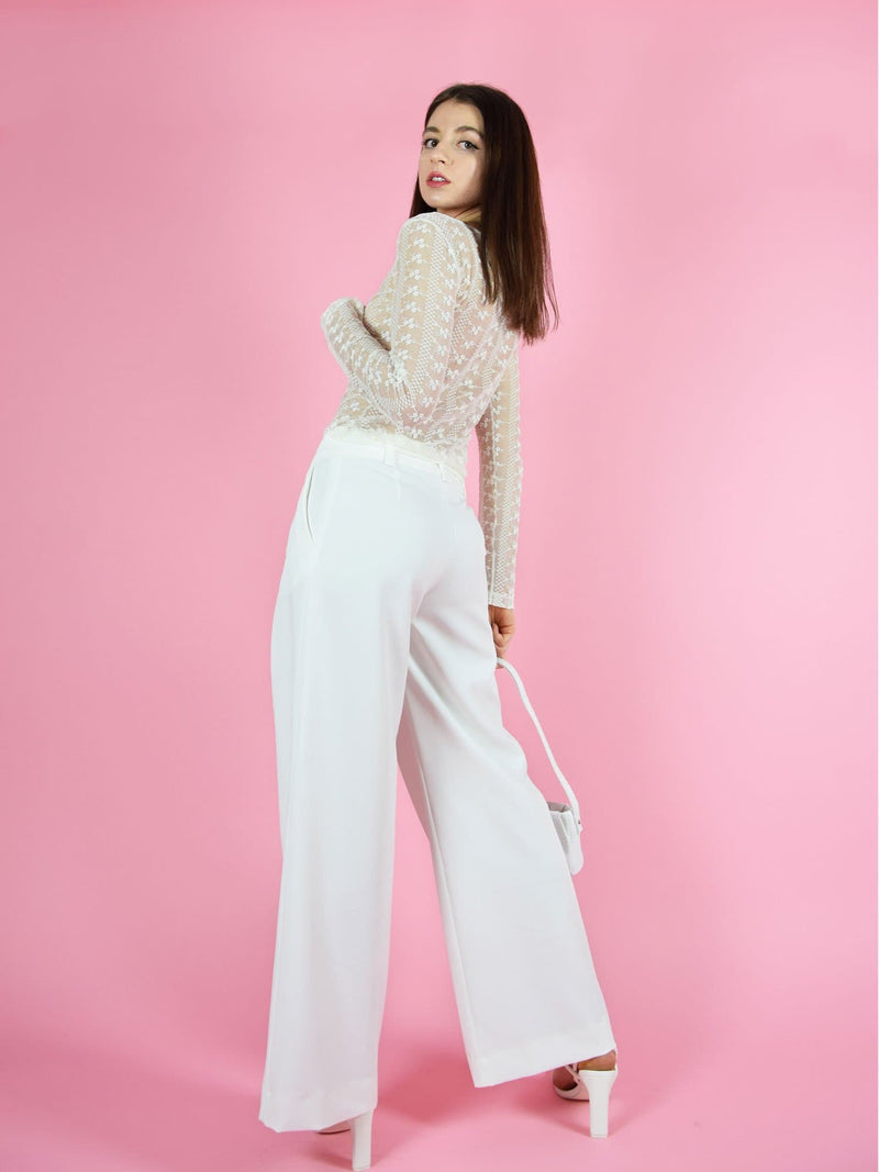 Backshot of blonde gone rogue's girlboss sustainable wide leg trousers in white. The trousers feature wide-leg design for comfort and freedom of movement.