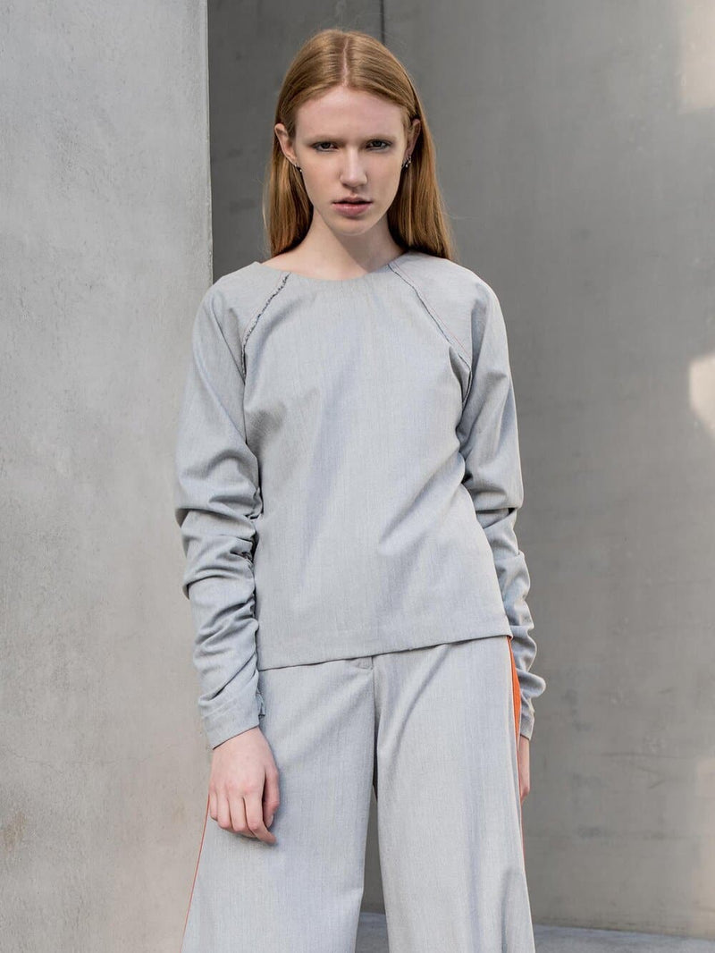 Woman wearing a grey herringbone winter blouse with gathered sleeves