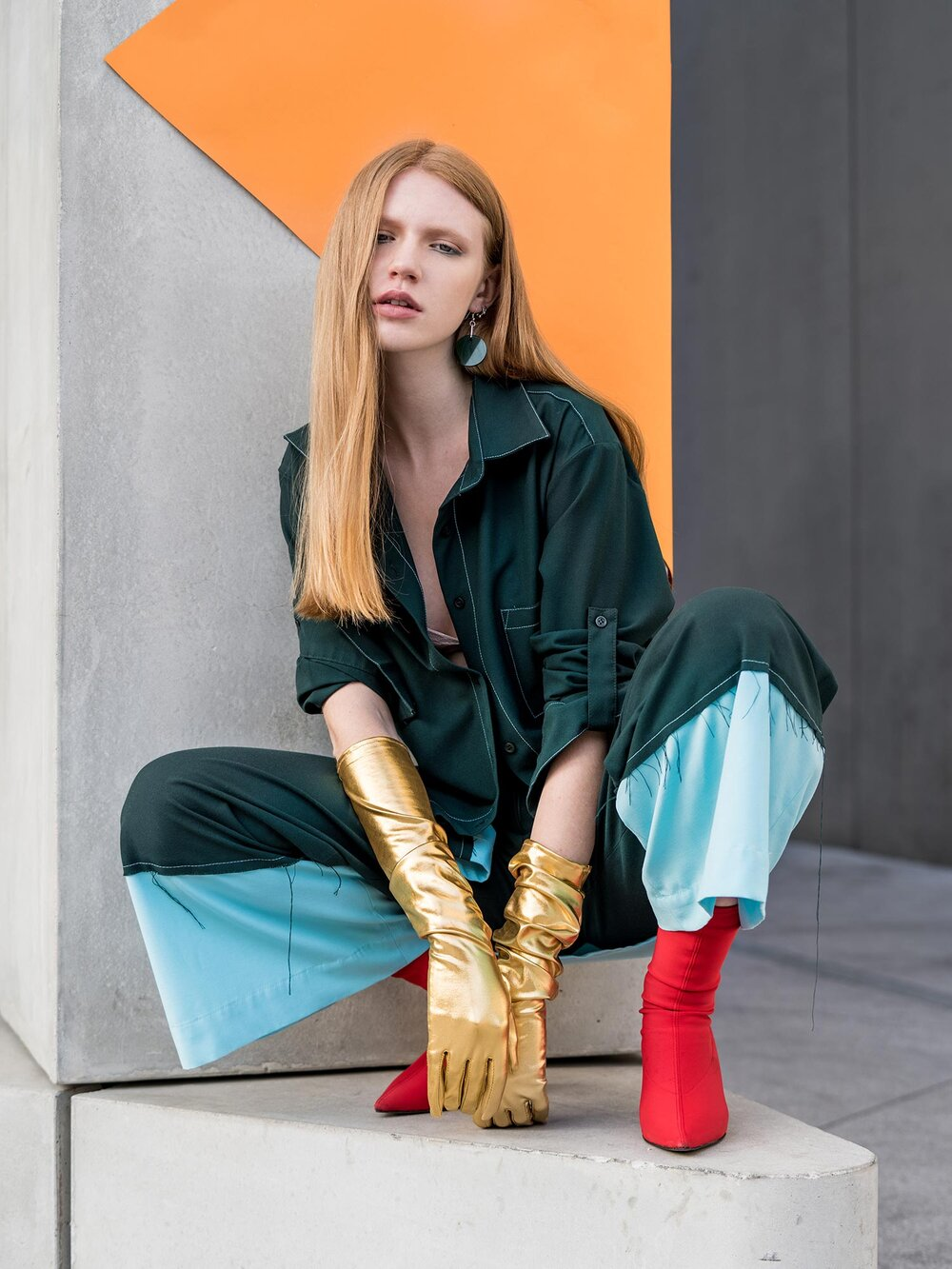 Woman wearing red boots, flared military green trousers and oversized shirt