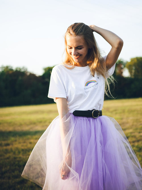 Woman in nature wearing a white sustainable recycled cotton tee with print and purple skirt