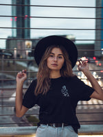 Woman on the street wearing a black sustainable tee and a hat