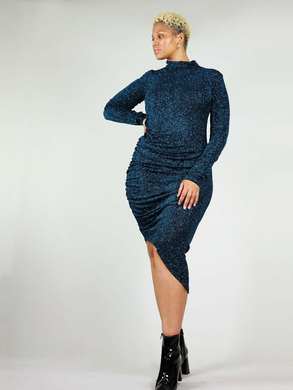 The new year's midi dress comes in sparking teal colour and is made from stretchy fabric to give you a perfect fit. It has asymmetric design that gathers on the side. Low turtleneck and long sleeves.