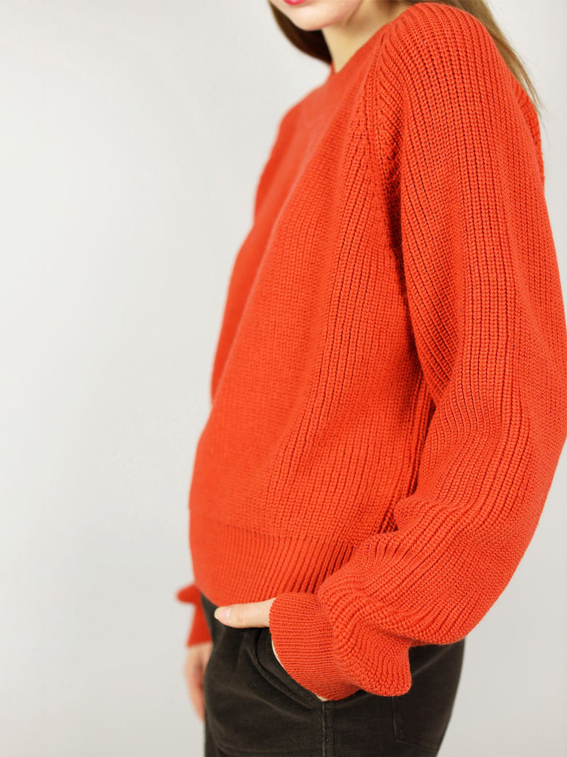 Side view of the organic sweater. It has bright, tomato red colour and slightly oversize fit. Long sleeves and crew neck.