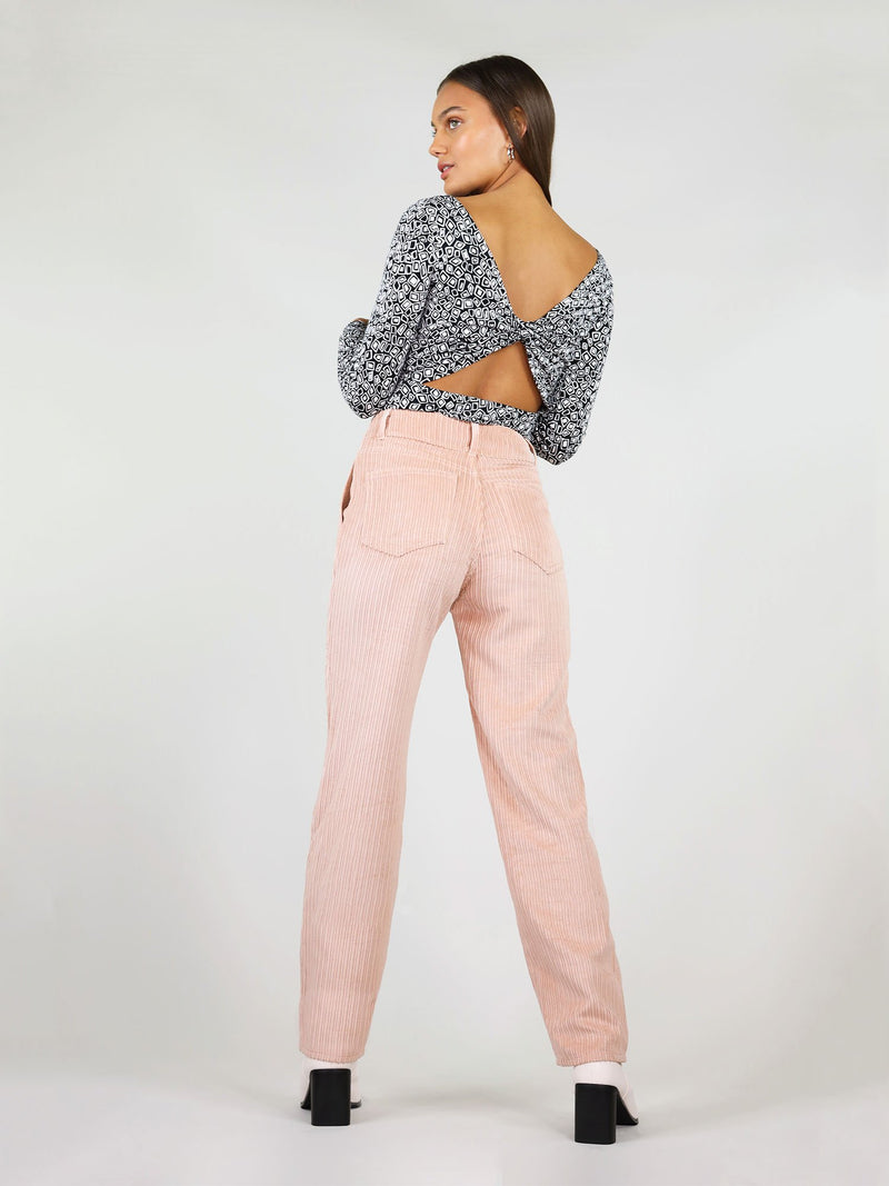 Back shot of the corduroy trousers in pastel pink. High waist and straight leg fit, with two large back pockets. Loose fit and belt loops.
