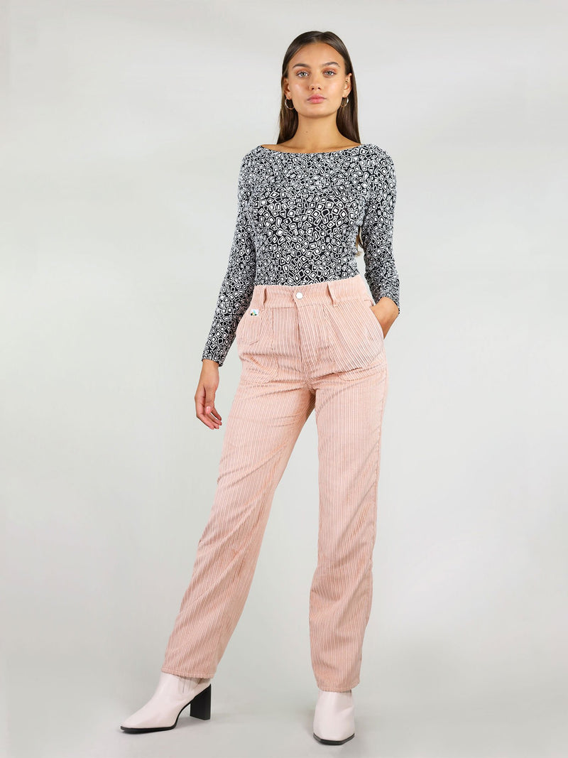 Full body shot of the high waist, pastel pink, corduroy trousers. Straight leg fit and button fastening. Two large side pockets with signature logo on the left side.