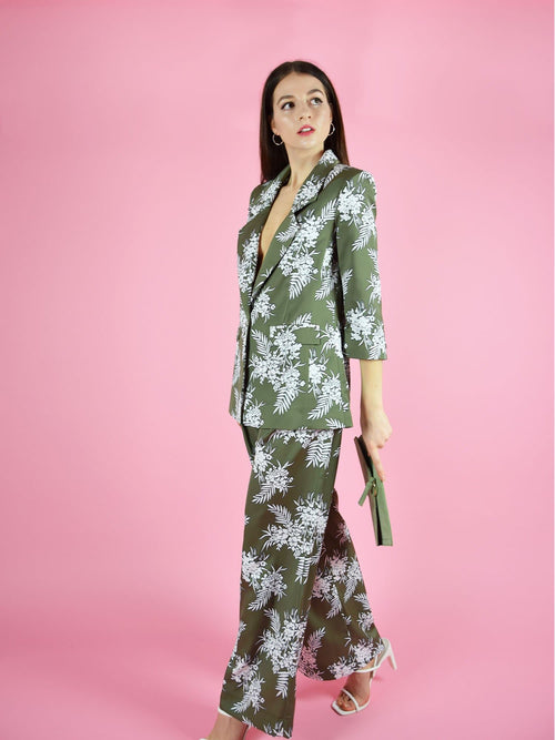 Sideshot of the sustainable trouser suit by blonde gone rogue. The pant suit consists of green with white print longline blazer and wide leg trousers.