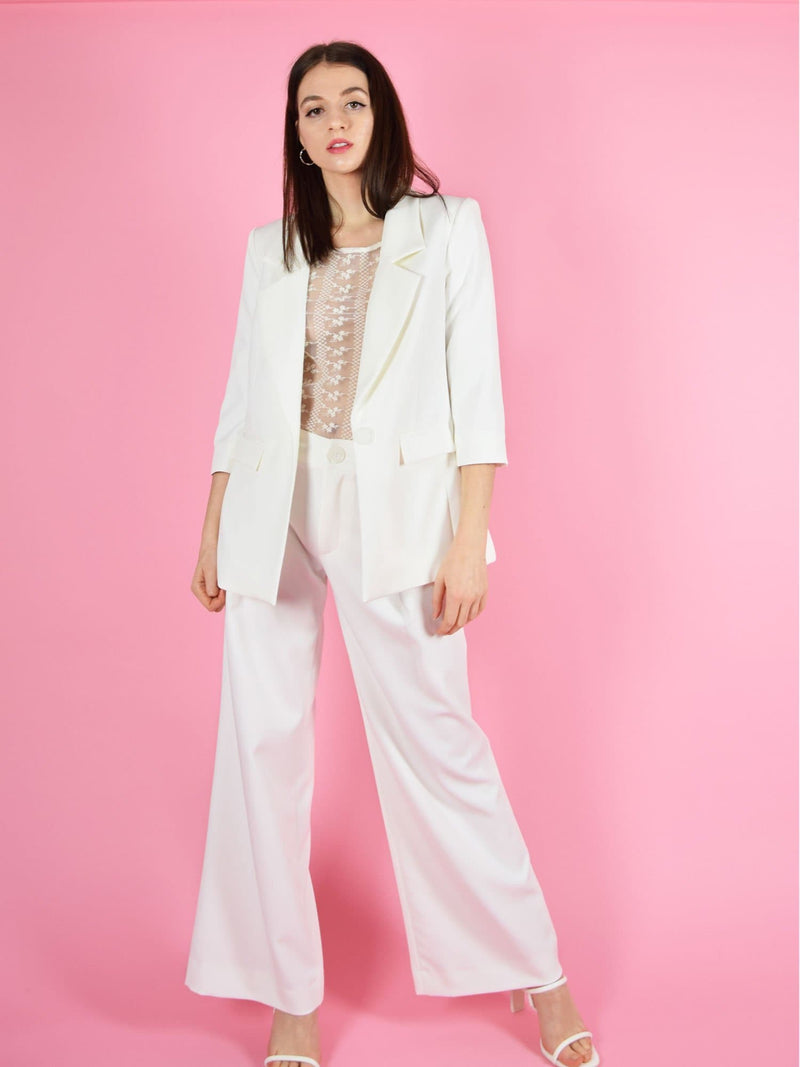 Frontshot of blonde gone rogue's girlboss white sustainable pant suit. The trouser suit is made from a brautiful floaty fabric and is perfect for formal occasions.