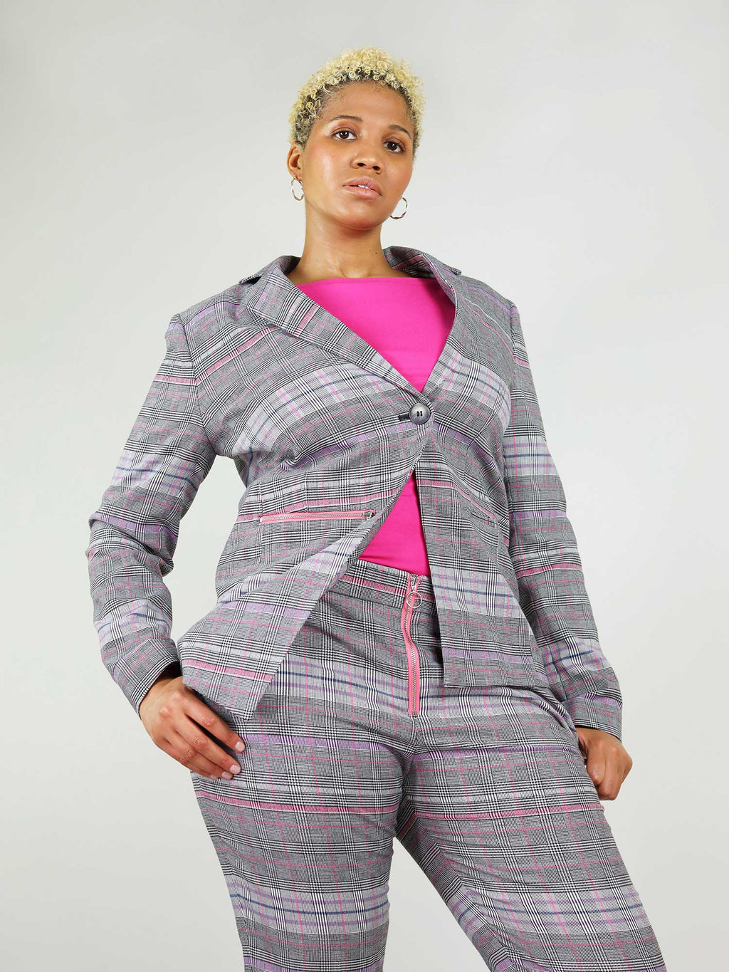 The revivify blazer has asymmetric shape and boxy fit as well as button fastening. Contrasting pink lining and different shades of grey.