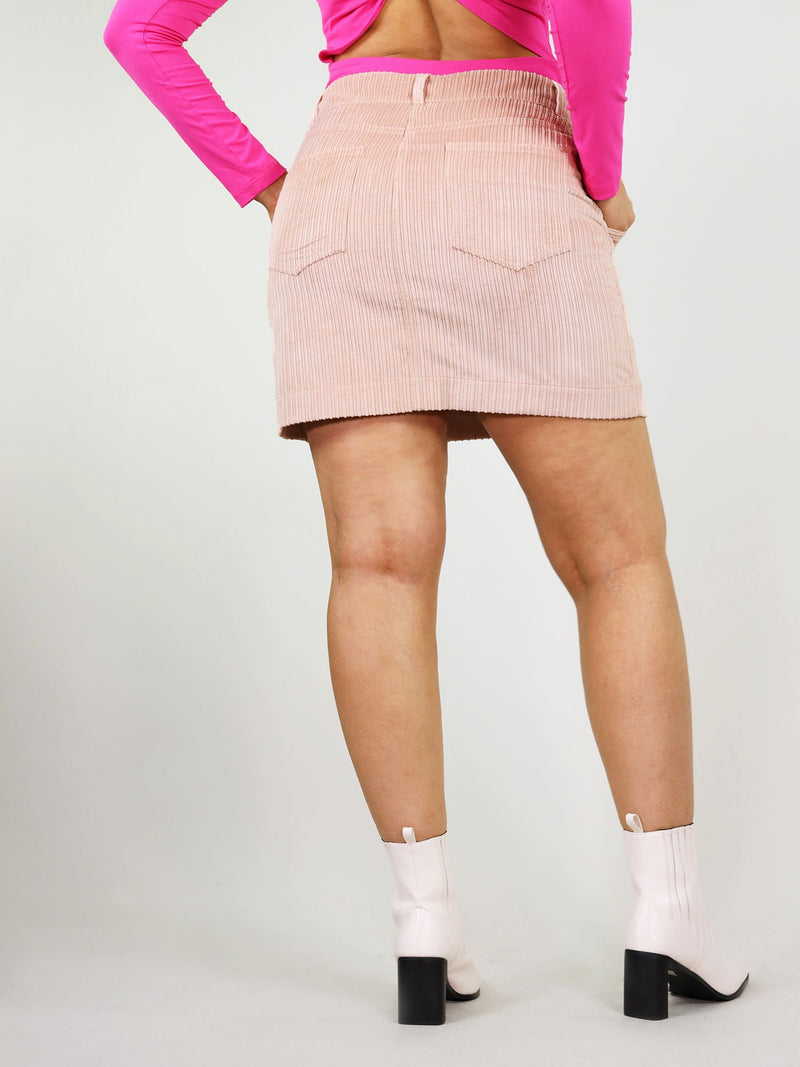 Size XL back shot of flirty pink corduroy skirt. Comfortable fit made from 100% organic cotton. Two back large pockets and mini length.