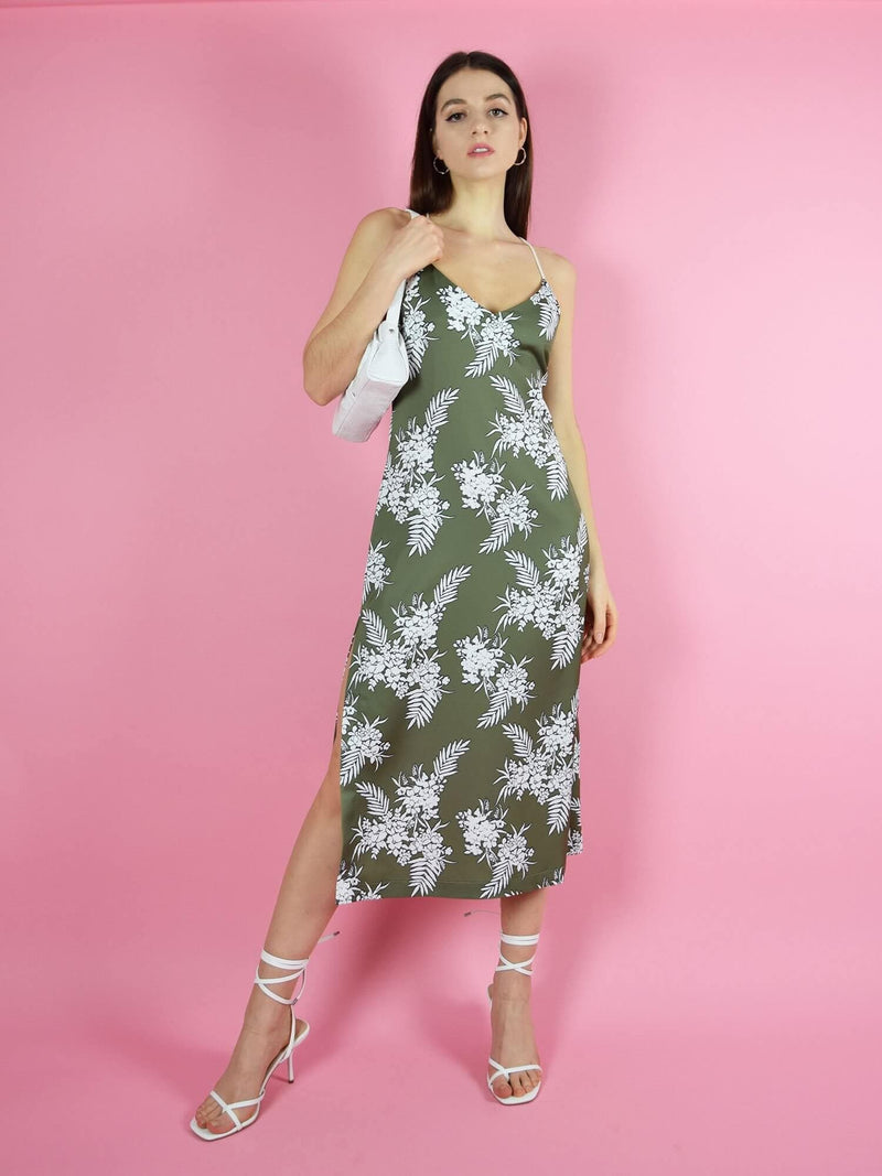 The midi slip dress with slit by blonde gone rogue is a cool, everyday dress is an open back. It comes in dark green with floral print in white.