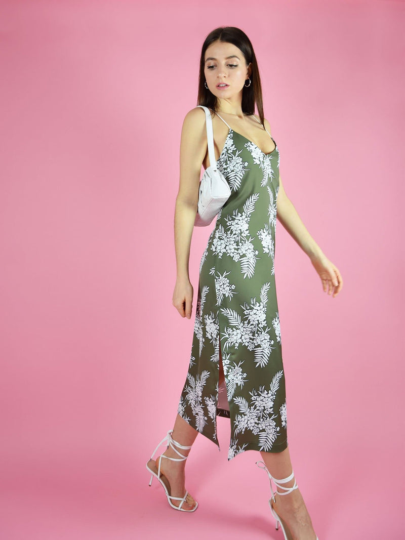 Motion shot of blonde gone rogue's midi slip dress in green paired with white high-heel sandals.