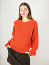 Slightly oversized, the organic sweater comes in bright tomato red. It has slightly oversized fit and crew neck.