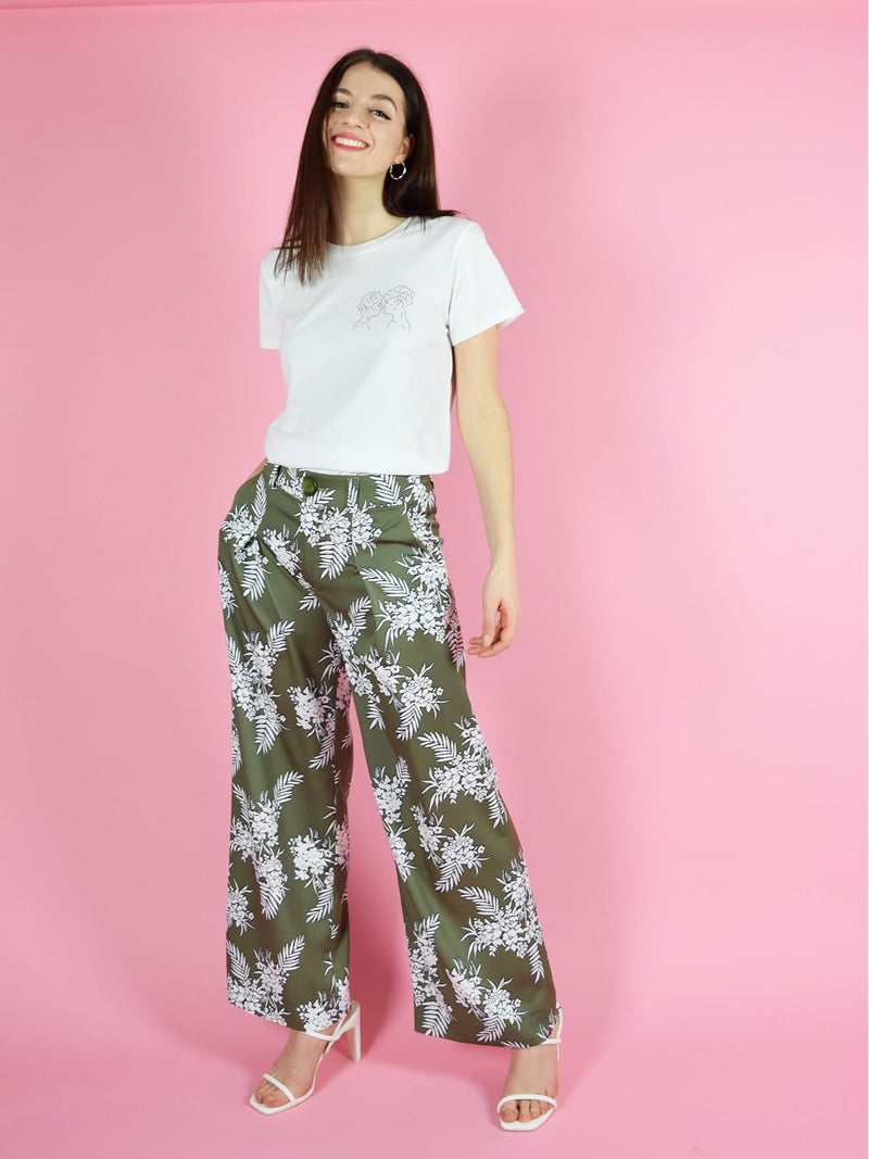 Frontshot of blonde gone rogue's lover's eyes organic cotton tee in white and the girlboss high wasited trousers in green with white floral print.