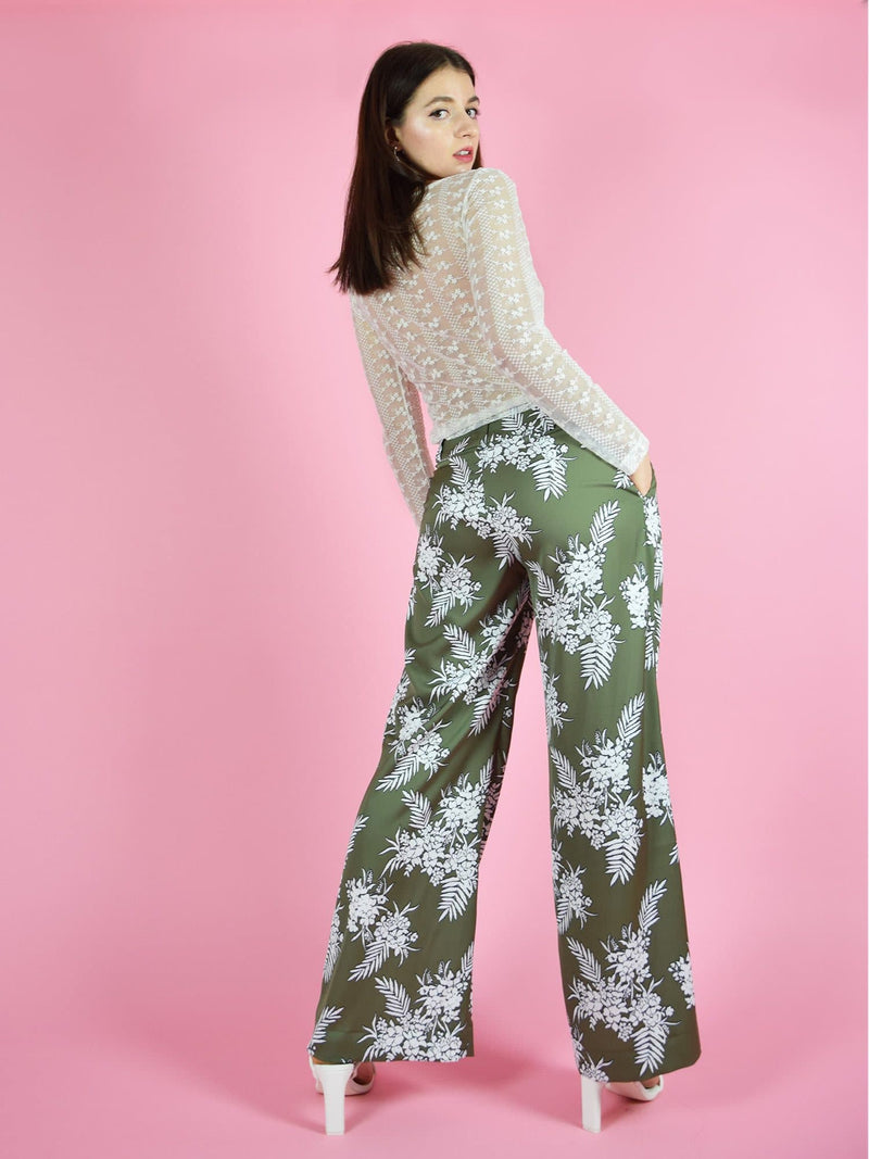 Backshot of blonde gone rogue's girlboss wide leg sustainable trousers in green and the daisy long sleeve tight fit lace top.