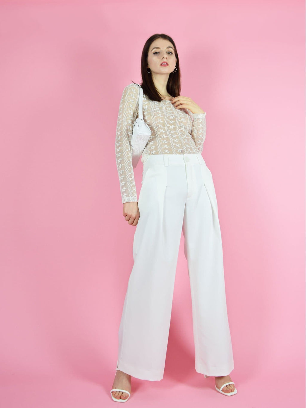 blonde gone rogue's girlboss sustainable trousers in white perfect for wedding guests and other formal occasions. The pants are paired with the daisy long-sleeve lace top in white.