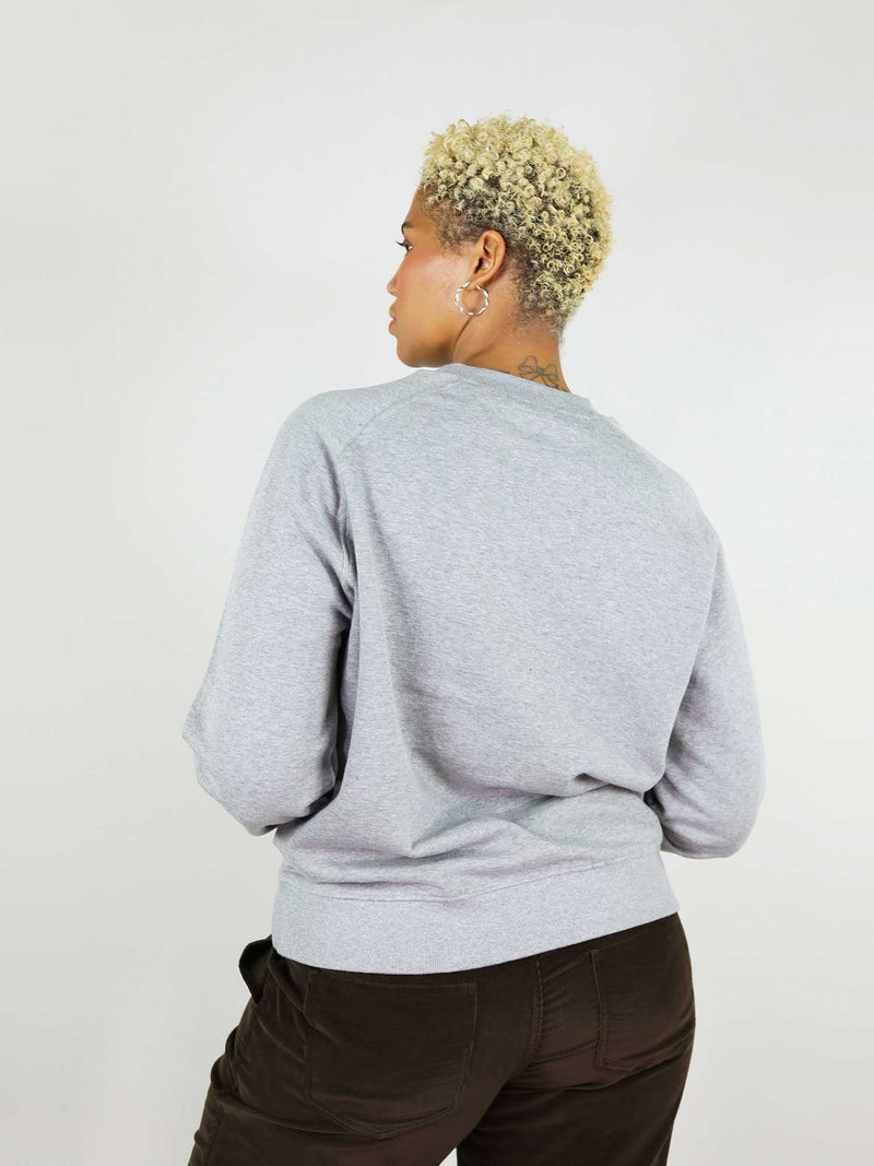 Back of the heart organic sweatshirt in grey is a relaxed, slightly oversized fit. Soft to the touch, 100% cotton. Raglan sleeves and crew neck.
