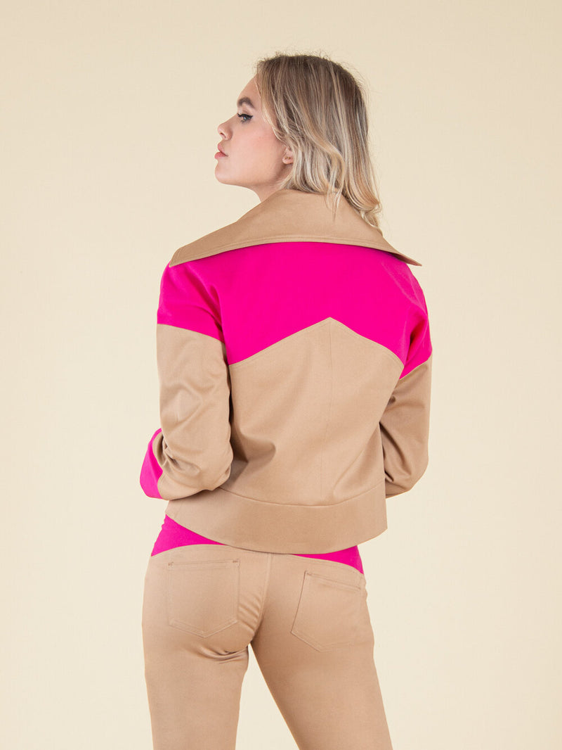 Backshot of a woman wearing a sustainable bomber jacket in beige with pink elements