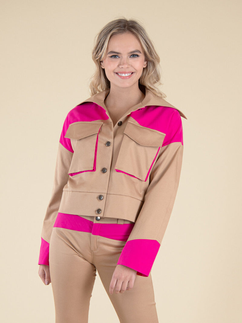 Frontshot of a woman wearing a upcycled beige bomber jacket with pink details