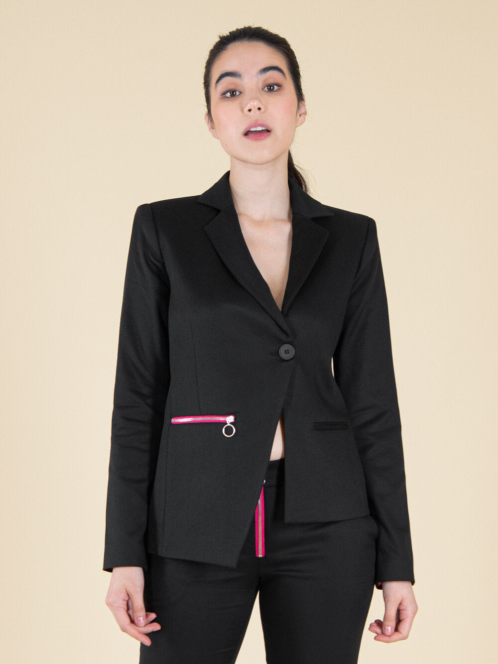 Woman wearing a black sustainable blazer with bright pink zipper