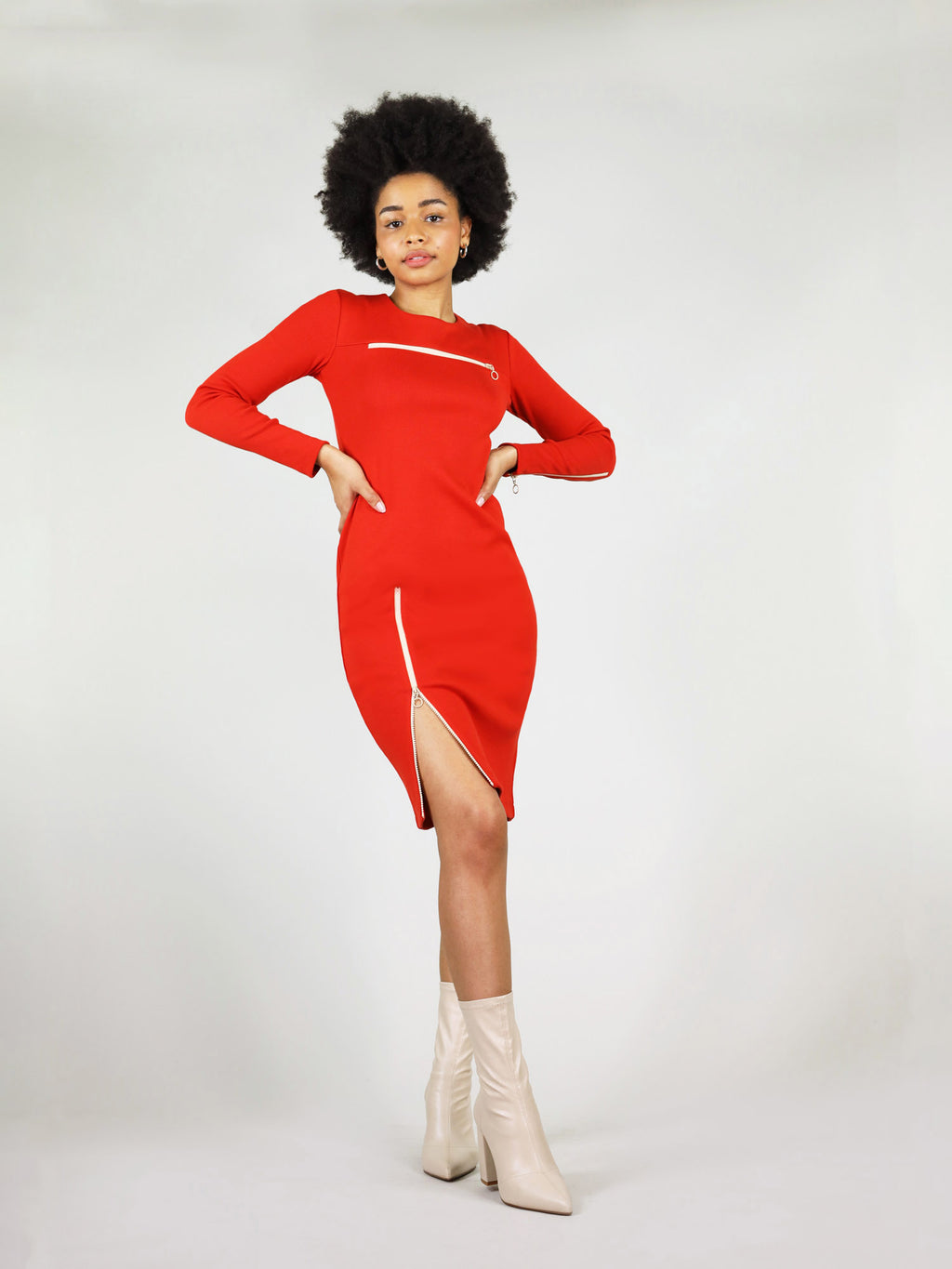 The wicked zipper dress in red has long sleeves with a white zip on the left arm, under knee length and white zip on the right leg that unzips, revealing the leg. Also has tight body con fit.