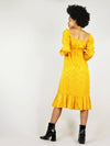 Full back body shot of mustard yellow empire dress in size XS. Beautiful, shinny fabric and relaxed fit with elastic at the cuffs and around the shoulders. Pleated bottom and ankle length.