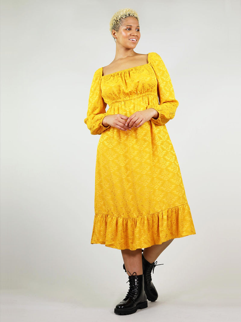 Size XL full body shot of empire dress in mustard yellow, square neck. Long sleeve and ankle length. Comfortable fit with elastic around cleavage, shoulders, and cuffs.
