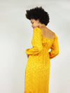 Back shot of size XS empire dress in mustard yellow. Elastic around the shoulders and backless square design. Long sleeve and elastic around the cleavage.