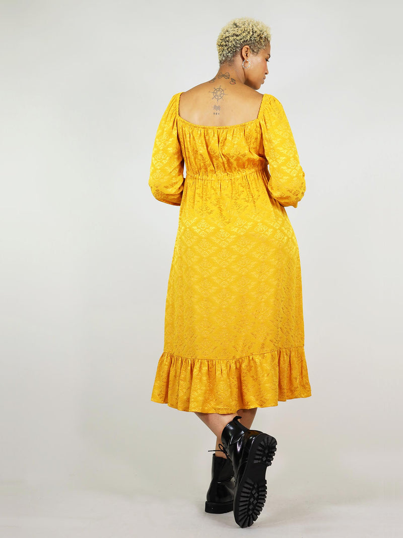 Backless square design and long sleeve. Mustard yellow empire dress is a fantastic fit for any size. Ankle length and pleated bottom.