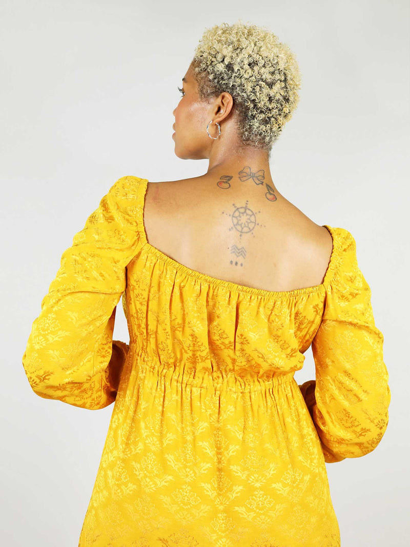 The empire dress in mustard yellow has backless square design with elastic around the shoulders and cleavage. It has long sleeve and elastic at the cuffs.