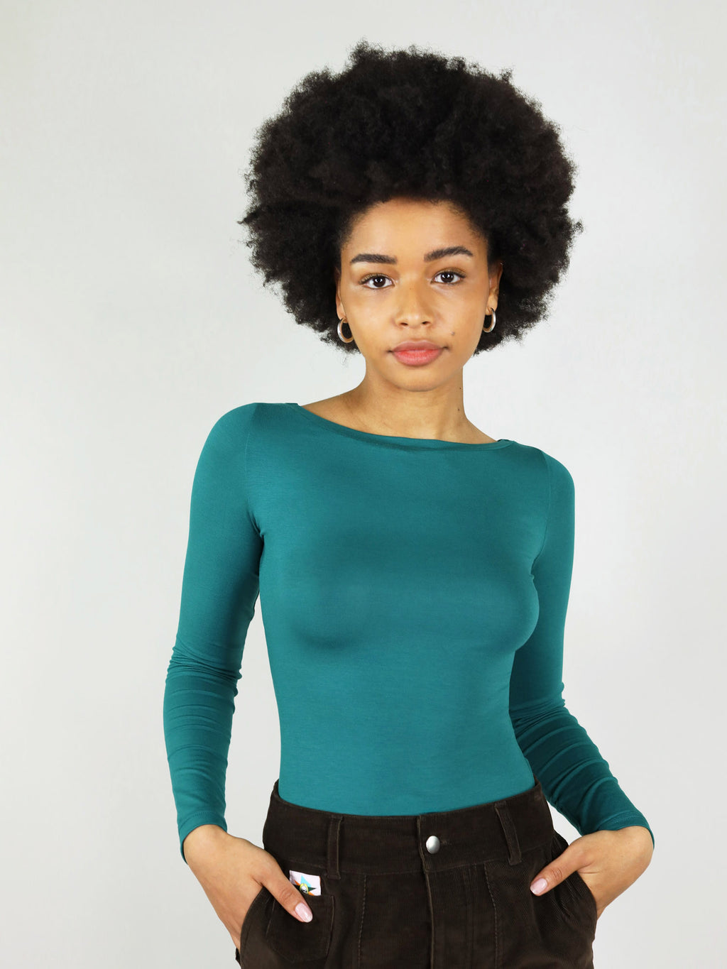 Twisted blouse in deep turquoise has fitted silhouette, long sleeves, and boat neck. 100% sustainable, made from 100% up-cycled deadstock.