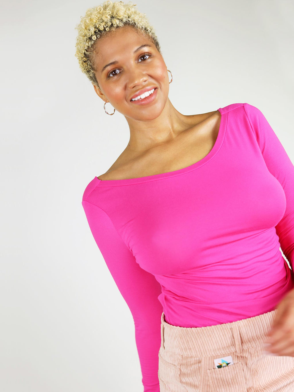 The candy pink twisted blouse is a fitted top with long sleeves and boat neck. It has body con silhouette and can be tucked in.