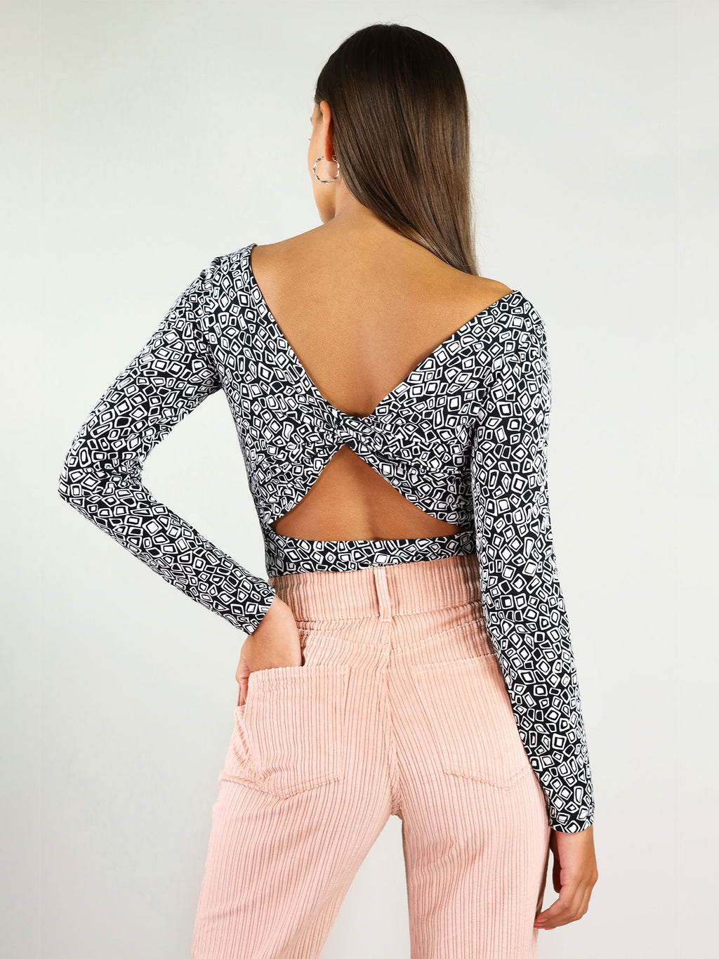 The twisted blouse has a white and black pattern and ribbon detail at the back. It has a semi-naked back and long sleeves.