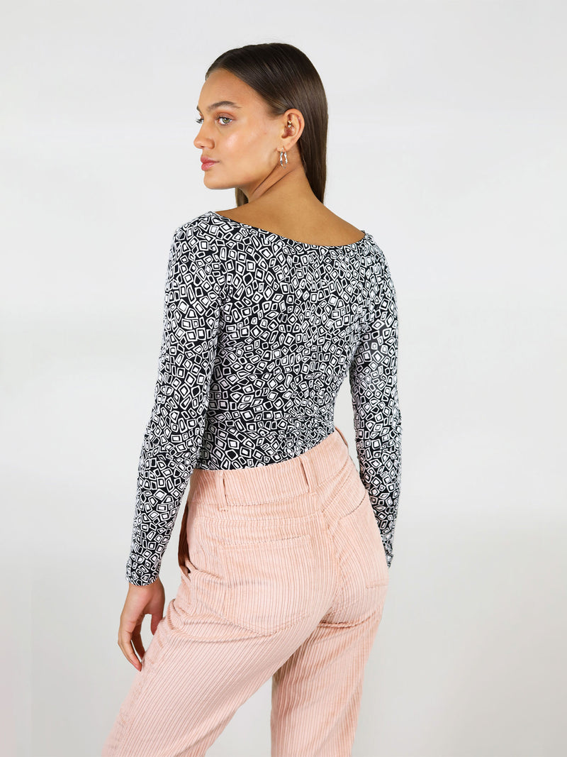 White and black pattern, the twisted blouse is a beautiful, fitted top with body con silhouette. Long sleeves and covered back.