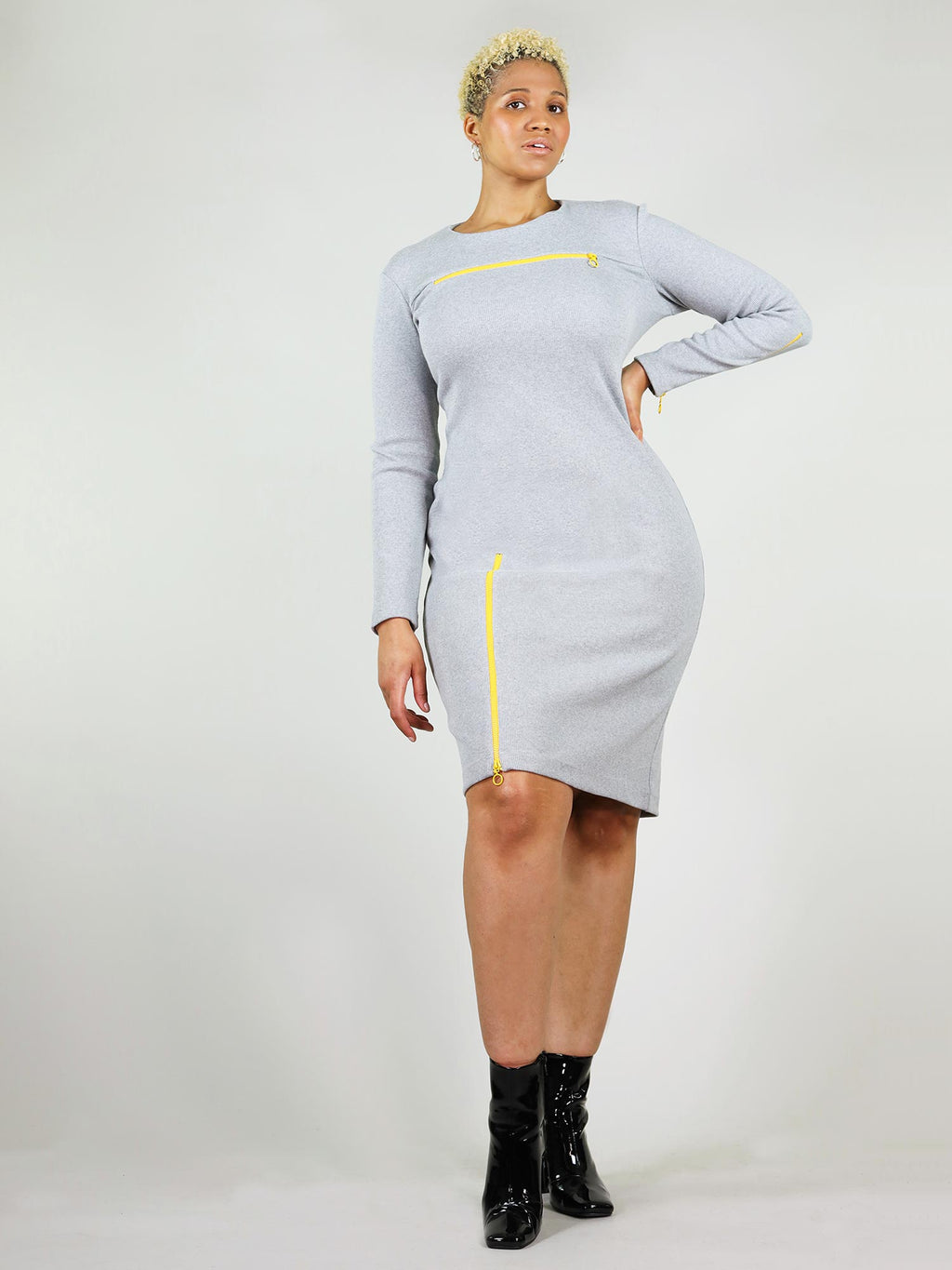 The wicked zip dress is grey has tight body con fit and under knee length. It has bright neon yellow zippers, one on the right leg and one under the collar bone area that can both unzip.