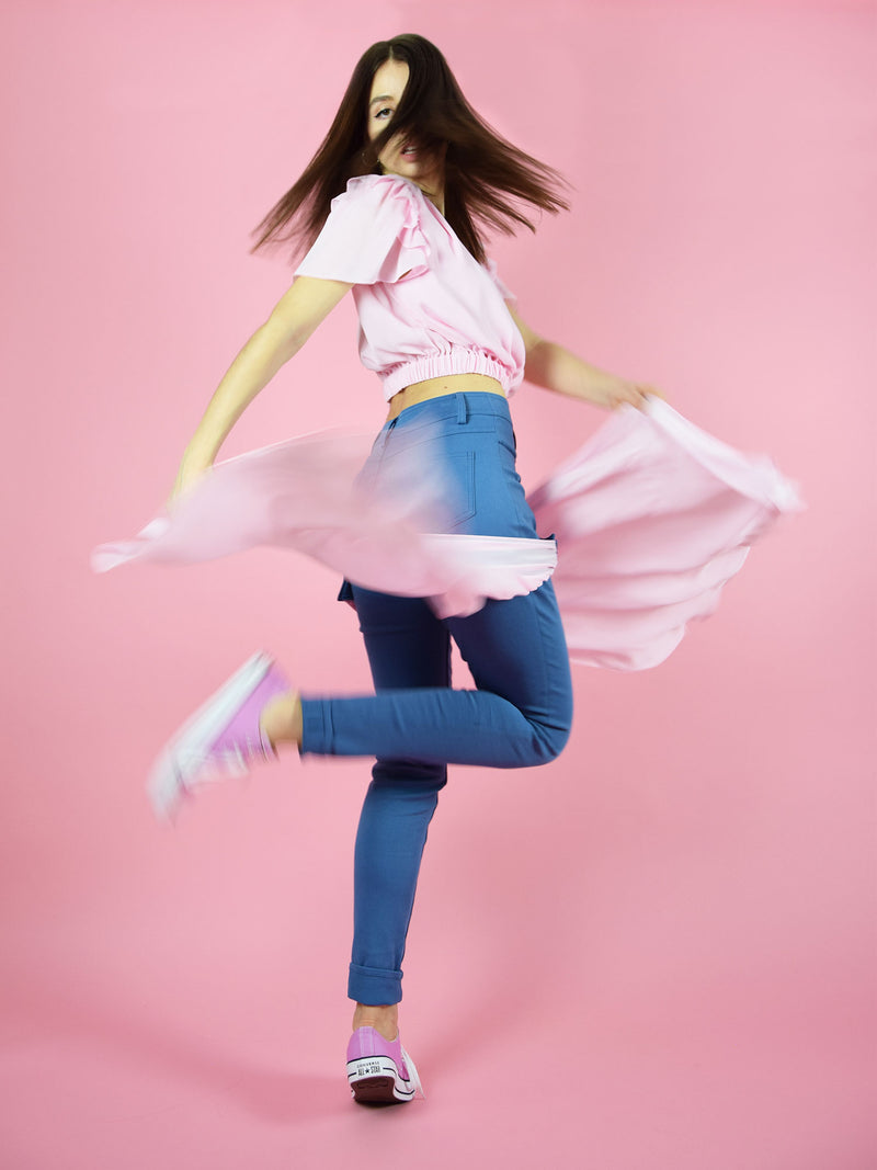 a creative shot of blonde gone rogue's summer outfit in pink - the set of wildflower surplice crop top and the skinny sustainable jeans.