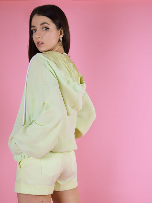 Backshot of blonde gone rogue's bonfire bomber jacket in green. The jacket is made from chiffon, has a lightweight, a hood and side pockets.
