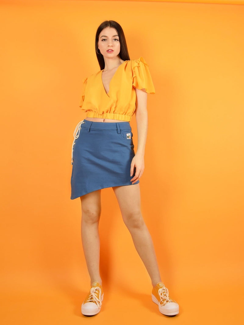 Frontshot of a cool outfit by blonde gone rogue - the wildflower surplice crop top in orange and the lace up sustainable denim skirt.