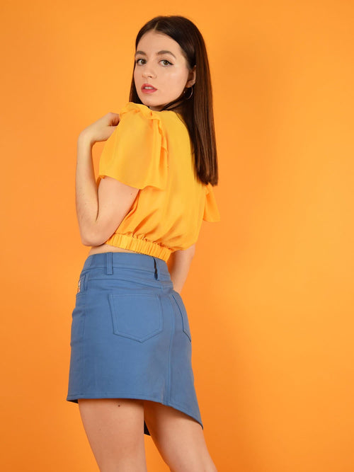 Backshot of the lace up denim skirt and the wildflower orange surplice top by blonde gone rogue.