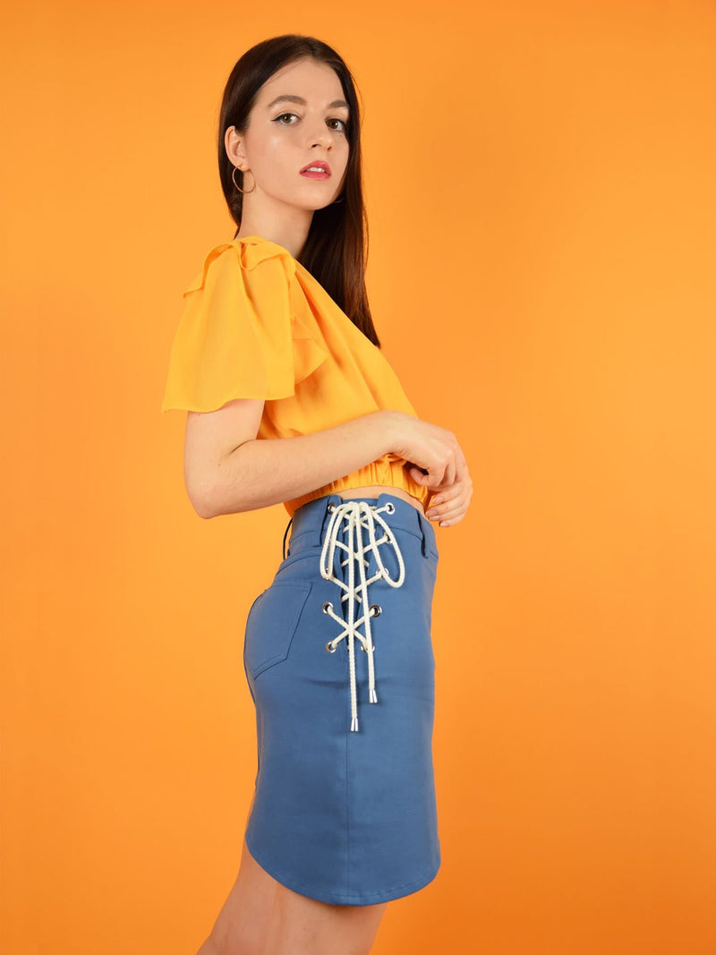 side shot of blonde gone rogue's lace up short denim skirt and wildflower sustainable surplice top in orange.