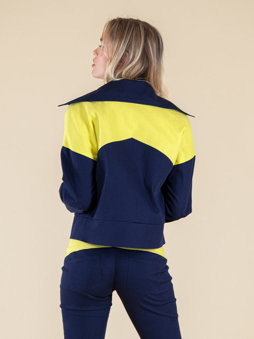Backshot of a woman wearing a navy blue sustainable jacket with yellow details