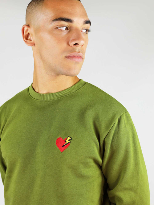 Closer view at the heart and thunder embroidery. Crew neck and regular, comfortable fit. Made from 100% organic cotton.