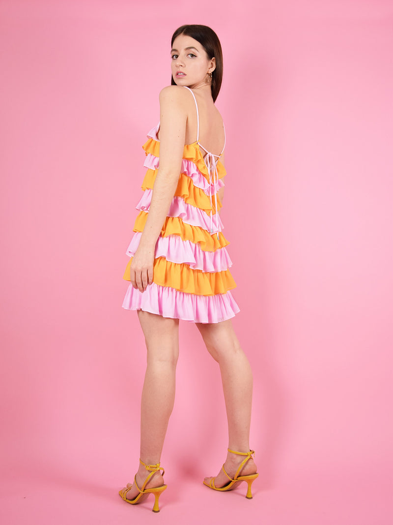 Backshot of the summer affair sustainable mini dress in pink and orange by blonde gone rogue.
